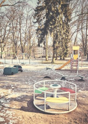 Retro toned picture of an empty outdoor playground in winter.