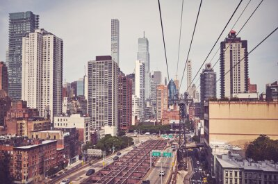 Retro toned picture of Manhattan skyline seen from the cable car, New York City, USA.