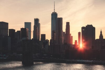 Retro toned picture of Manhattan skyline silhouette at sunset, New York City, USA.