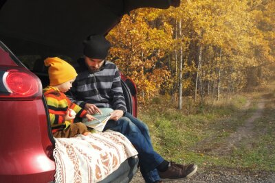 Obraz Road trip in fall season, family travel, self-guided journey. Father and child boy looking on map and pointing route, while sitting in car trunk in autumn forest.