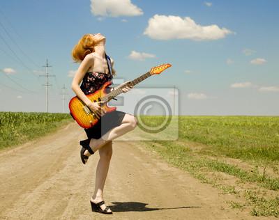 Rock dziewczyna z gitarą na wsi.