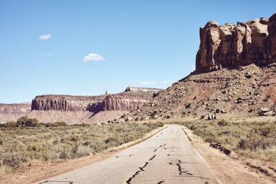 Rock formations by a road in Canyonlands National Park, color toning applied, Utah, USA.