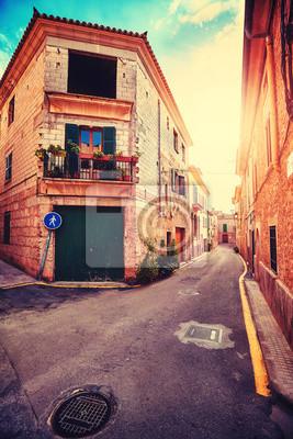 Rocznik stylizowana wąska ulica w Alcudia starym miasteczku przy zmierzchem, Mallorca, Hiszpania.