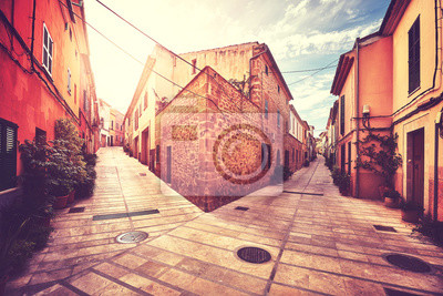 Rocznika stylizowany obrazek róg ulicy w Alcudia starym miasteczku przy zmierzchem, Mallorca, Hiszpania.