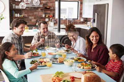 Obraz Rodzina Multi generacji korzystających posiłek wokół stołu w domu razem