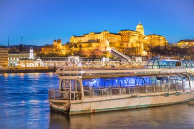 Romantic ferry at sunset in Budapest along Danube river with view on city castle, Hungary