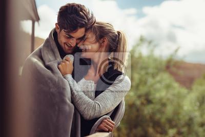 Obraz Romantyczna para owinięta w koc na zewnątrz