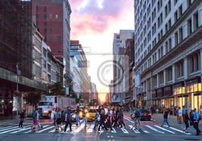 Różnorodna grupa ludzi spacerująca po ruchliwym skrzyżowaniu 23 ulicy i 6th Avenue na Manhattanie z kolorowym światłem zachodzącego słońca przeświecającym przez budynki skyline