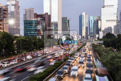 Ruch w godzinach szczytu uchwycony z rozmytym ruchem wzdłuż autostrady Gatot Subroto w sercu biznesowej dzielnicy Dżakarty w stolicy Indonezji o zmierzchu