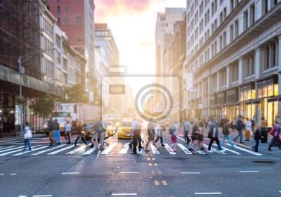 Ruchliwe skrzyżowanie 23rd Street i 5th Avenue na Manhattanie z tłumami różnorodnych ludzi przechodzących przed samochodami i taksówkami w Nowym Jorku