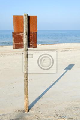 Rusty szyld na drewnianych post na plaży.