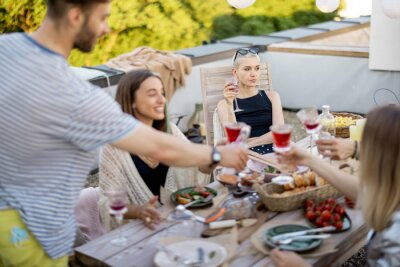 Obraz Sad and thoughtful woman sitting separately on a party with friends outdoors, young people dining on a rooftop terrace