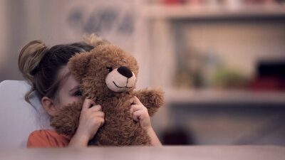 Obraz Sad female kid covering face by teddy bear toy, family problem, loneliness abuse