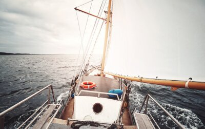 Sailing against the sun, color toned picture of an old schooner.