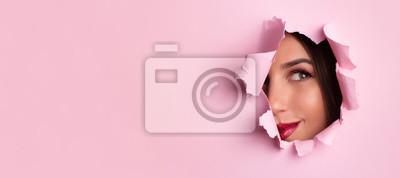 Obraz Salon kosmetyczny banner reklamowy z miejsca kopiowania. Piękni dziewczyn spojrzenia przez dziury w menchiach tapetują tło. Wizażysta, moda, koncepcja piękna. Sprzedaż kosmetyków.