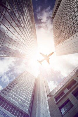Obraz Samolot lecący nad nowoczesnych wieżowców biurowych