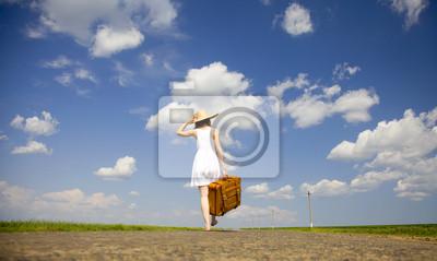 Samotna dziewczyna z walizką na drodze kraju.