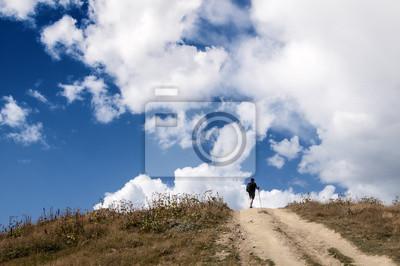 samotny wędrowiec na szczycie wpatrzony w błękit Nieba