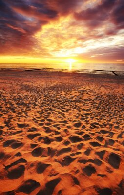 Sandy beach at beautiful sunset with dramatic sky.