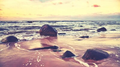 Scenic beach with stones at sunset, color toning applied.