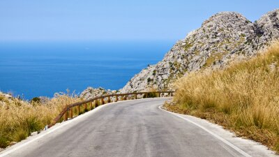 Scenic mountain road bend with sea in distance, Mallorca, Spain.