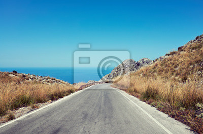 Scenic mountain road with sea in distance, color toning applied, Mallorca, Spain.