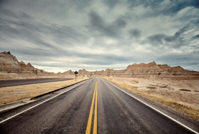 Scenic road in Badlands National Park, color toning applied, travel concept, USA.
