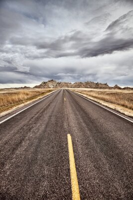 Scenic road in Badlands National Park, color toning applied, USA.