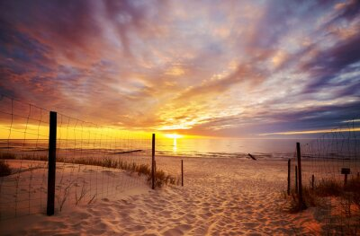 Scenic sunset over Baltic Sea beach with dramatic cloudscape, Poland.