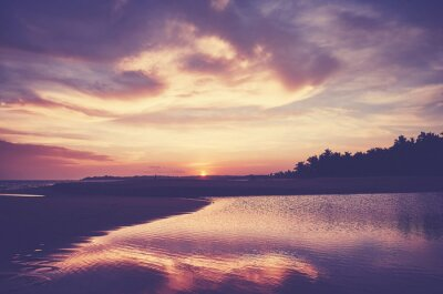 Scenic sunset reflected in water, color toned picture.