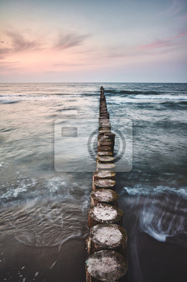 Scenic sunset with a wooden sea breakwater, color toning applied, long exposure.