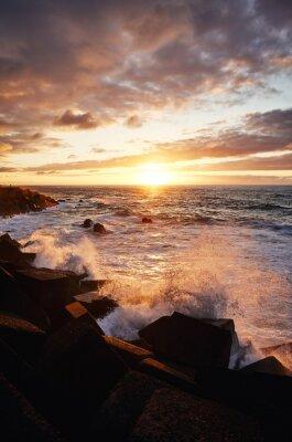 Scenic sunset with waves crashing on rocks, Puerto de la Cruz, Tenerife, Spain.