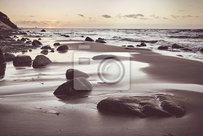 Sceniczna plaża z kamieniami przy zmierzchem, selekcyjna ostrość, stosuje tonowanie kolor.