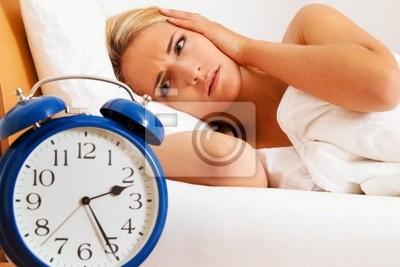 Schlaflos mit Uhr in der Nacht. Frau kann nicht sc