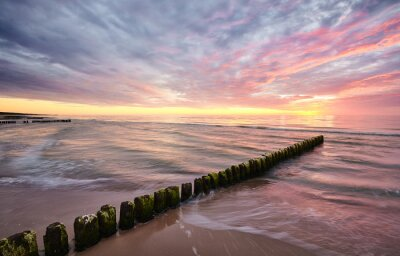 Seascape with an old wooden breakwater at sunset.
