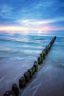 Seascape with an old wooden breakwater at sunset, long exposure picture.