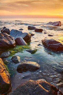 Seascape with rocks in water at sunset.
