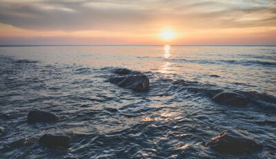 Seascape with rocks in water at sunset, Miedzyzdroje, Poland.