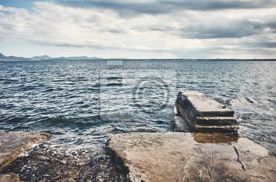 Seascape z betonowym pomostem, zdjęcie w stonowanych kolorach.