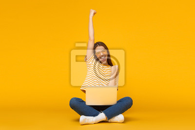 Obraz She is a winner! Excited young female with laptop isolated on yellow background