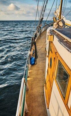 Side of an old sailing schooner at sunset, color toning applied.