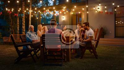 Obraz Siedząc przy stole obiadowym Przystojny młody człowiek gra na gitarze dla przyjaciół. Rodzina i przyjaciele słuchają muzyki podczas uroczystości w ogrodzie.