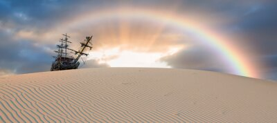 Obraz Silhouette of old ship on desert with rainbow at amazing sunset