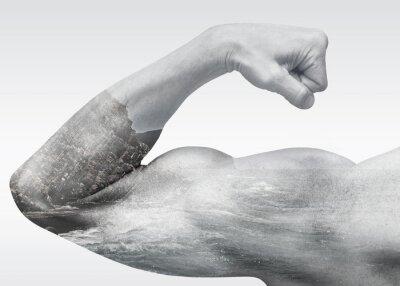 Obraz Silny mężczyzna ręka pokazuje biceps z wybrzeża morskiego krajobrazu