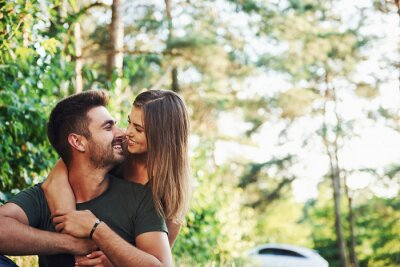 Obraz Sitting and embracing. Beautiful young couple have a good time in the forest at daytime