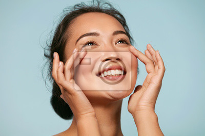 Obraz Skin care. Woman with beauty face touching healthy facial skin portrait. Beautiful smiling asian girl model with natural makeup touching glowing hydrated skin on blue background closeup