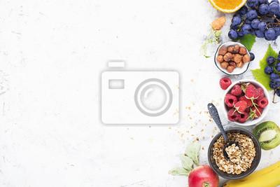 Obraz Składniki na zdrowe posiłki śniadaniowe: maliny, jagody, orzechy, pomarańcza, banany, winogrona niebieskie, zielone, jabłka, kiwi. Widok z góry.
