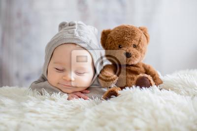 Obraz Słodka chłopiec w niedźwiadkowym kombinezonie, dosypianie w łóżku z misiem