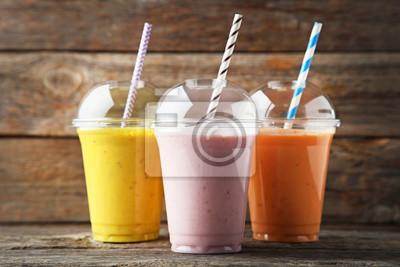 Obraz Słodki smoothie w plastikowych filiżankach na drewnianym stole