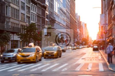 Słońce świeci przy ruchliwej ulicy w Nowym Jorku z taksówkami zatrzymanymi na skrzyżowaniu